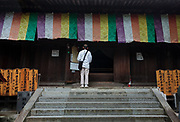 A Pilgrim, known as a Henro, prays at Ishite temple on the Shikoku 88 Temple pilgrimage, Matsuyama, Eihime, Japan.. Friday, June 26th 2015