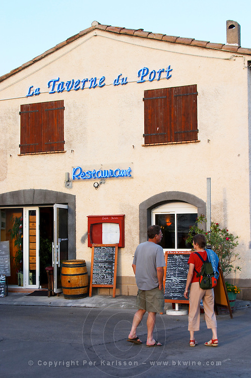 La Taverne du Port with many chalkboards with menus. A couple reading the offers. Marseillan. Languedoc. France. Europe.