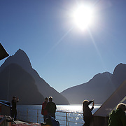 Tourists on a cruise ship on Milford Sound with Mitre Peak in the distance. .Milford Sound (Piopiotahi in Ma¯ori) is a fjord in the south west of New Zealand's South Island, within Fiordland National Park and the Te Wahipounamu World Heritage site. It has been judged the world's top travel destination and is acclaimed as New Zealand's most famous tourist destination..Milford Sound runs 15 kilometres inland from the Tasman Sea at Dale Point - the mouth of the fiord - and is surrounded by sheer rock faces that rise 1,200metres (3,900ft) or more on either side. Among the peaks are The Elephant at 1,517metres (4,977ft), said to resemble an elephant's head and The Lion, 1,302metres (4,272ft), in the shape of a crouching lion. Lush rain forests cling precariously to these cliffs, while seals, penguins, and dolphins frequent the waters and whales can be seen sometimes..Milford Sound sports two permanent waterfalls all year round, Lady Bowen Falls and Stirling Falls. After heavy rain many hundreds of temporary waterfalls can be seen running down the steep sided rock faces. .The beauty of this landscape draws thousands of visitors each day, with between 550,000 and 1 million visitors in total per year. This makes the sound one of New Zealand's most-visited tourist spots, and also the most famous New Zealand tourist destination.  Milford Sound, New Zealand. 29th April 2011. Photo Tim Clayton