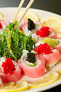 Chopsticks pick up seaweed salad surrounded by a sushi roll with roe and lemon slices.