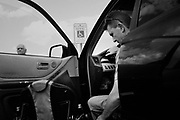 """BIRMINGHAM, AL – JUNE 13, 2015: Matthew Seals, 47, prepares to transition between car and wheelchair during a trip to get groceries. <br /> <br /> In April 1998, a deadly F5 tornado ripped through the suburbs of Birmingham, Alabama, killing 32 people and destroying hundreds of homes. Seventeen years later, Matthew Seals is still learning to cope with the loss of his youngest son, who was killed in the storm. With help from Habitat for Humanity, Seals completed construction on a new home in 2015, where he continues to raise his remaining children and his new life as a paraplegic. Despite his own suffering from the tragedy, Seals volunteers with Habitat to help other families find their own form of stability through home ownership. """"Habitat gives you an opportunity to help yourself,"""" Seals said. """"Not just for the immediate need, but for the long term to become more self-sufficient, more self-confident, and more self-reliant."""""""