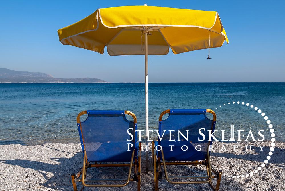 Samos. Greece. Two folding blue beach chairs and a large yellow beach umbrella on a pebbly beach on the southeast coast of Samos.