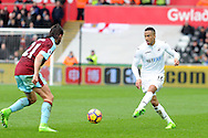 Swansea's Martin Ollson (r) passes the ball past Burnley's George Boyd. Premier league match, Swansea city v Burnley at the Liberty Stadium in Swansea, South Wales on Saturday 4th March 2017.<br /> pic by  Carl Robertson, Andrew Orchard sports photography.