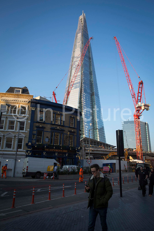 Commuters on Tooley Street with The Shard and The News Building in the background in London, United Kingdom. The iconic design of The Shard was inspired by the spires of London churches and masts of tall, 18th-century ships.