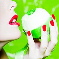 beautiful caucasian woman portrait holding a peeled apple studio on green background