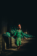 A man dressed in the traditional Khmer costume of the Robam Kngaok Pailin Peacock dancer in the sunlight filtering through the cloistered temple windows, Angkor Wat, Siem Reap, Cambodia