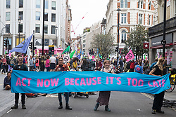London, UK. 23rd August, 2021. Environmental activists from Extinction Rebellion hold a banner in front of a giant table used to block roads in the Covent Garden area during the first day of Impossible Rebellion protests. Extinction Rebellion are calling on the UK government to cease all new fossil fuel investment with immediate effect. Credit: Mark Kerrison/Alamy Live News