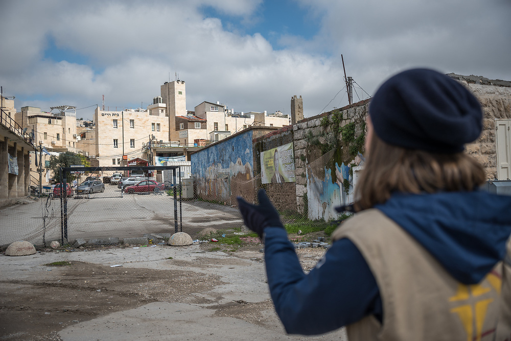 2 March 2020, Hebron: Nora, a participant in the World Council of Churches Ecumenical Accompaniment Programme in Palestine and Israel, points to a football field built by Israeli settlers on the Al-Shuhada Street in the H2 area of Hebron. The area is under Israeli military control, and following the 1994 massacre at the Tomb of the Patriarchs (known to the Muslims as Al-Ibrahimi Mosque and to the Jews as Cave of Machpelah) all the Palestinian shops on Shuhada street have been closed, turning the street into a virtual ghost town.