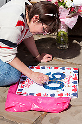 © Licensed to London News Pictures. 20/04/2016. Windsor, UK. Kathy Martin, 53, originally from Melbourne, Australia, now Beckenham, Kent, decorates a homemade birthday card and is one of the keen royal fans who will camp out overnight in order to be in prime position in order to see The Queen as she takes part in a walkabout outside Windsor Castle tomorrow her 90th birthday tomorrow. © Stephen Chung / Alamy Live News Photo credit : Stephen Chung/LNP