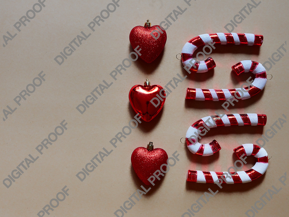 Christmas candy cane and hearts at studio above view over a brwon cream neutral background isolated flatlay