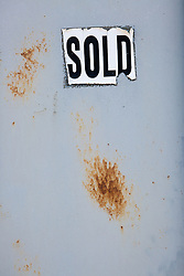 sold sign on decaying metal