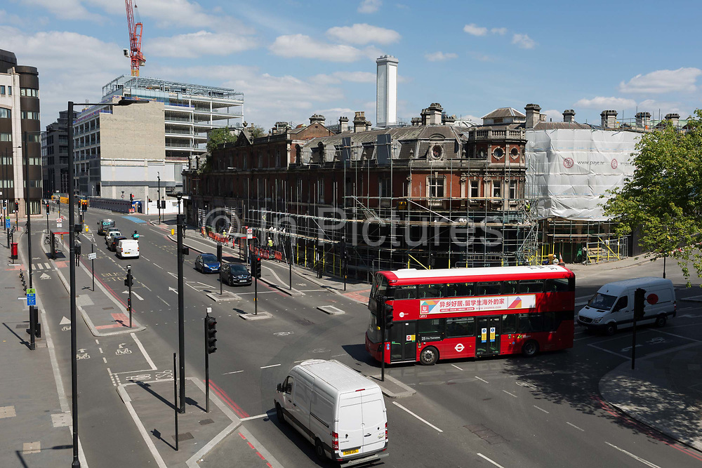 Seen from Holborn Viaduct, a red London bus pulls out across the road junction of West Smithfield and Farringdon Street, where scaffolding is being constructed on a facade of Smithfield Market which is undergoing a major redevelopment programme, on 15th May 2020, in London, England. The Museum of London revealed plans in 2015, to vacate its Barbican site and move into the General Market Building. The cost of the move is estimated to be in the region of £70 million and, if funding can be achieved, would be complete by 2021. There has been a market on this location since the Bartholomew Fair was established in 1133 by Augustinian friars.