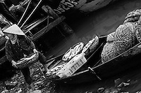 A woman unloads baskets of fish from her boat at the riverside  market.