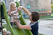 Mom helping apprehensive toddler down park slide. Balucki District Lodz Central Poland