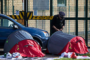A Kent Police officer monitors two Palestine Action activists in small tents locked onto a vehicle to block an entrance to the Instro Precision factory in Discovery Park on 4th October 2021 in Sandwich, United Kingdom. Instro Precision is a subsidiary of Israels largest publicly-traded arms company Elbit Systems supplying high precision military equipment and Palestine Action contends that Instro Precision equipment has been used by the Israeli military against the population of Gaza.