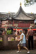 An elderly woman practices Tai Chi in front of the Huxinting Teahouse in Yu Yuan Gardens Shanghai, China