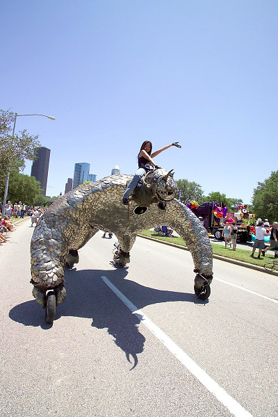 Stock photo of a woman riding on top of an odd shaped metallic car