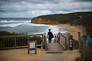 A surfer at Bells Beach walks down to the heavy surf near Torquay, Victoria, Australia. Famous for its surfing, the area is part of the Great Ocean Road.