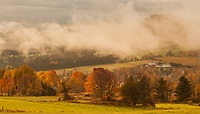 Early morning light burns through the fog adding warmth and depth to this bucolic scene outside Peacham, Vermont