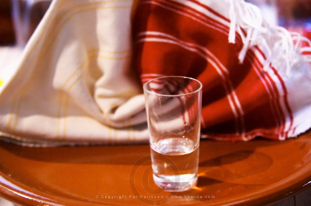 A small glass of UNK traditional spirit drunk as an aperitif. Tradita traditional restaurant, Shkodra. Albania, Balkan, Europe.