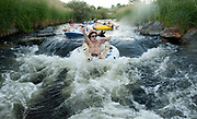 PRICE CHAMBERS / NEWS&GUIDE<br /> Nick Lietch holds his beer high as he drops into Flat Creek's rocky narrows. His group of friends put in near Dairy Queen to float the waterway downstream to Crabtree Park, a Jackson summer tradition.