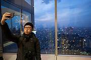 A male Asian tourist s takes a selfie photo with a smart phone on the 45th Floor Observation deck of the Tokyo Metropolitan Government Tower in Shinjuku., Tokyo, Japan. Thursday February 15th 2018