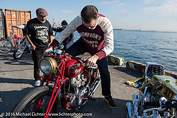 Bryan Thompson of Thompson Cycle starting the 1952 Pre-unit Triumph he built for skateboarding legend Steve Caballero (in background) at the Yokohama docks where bikes from invited USA custom builders were unloaded prior to the Mooneyes Yokohama Hot Rod & Custom Show. Yokohama, Japan. December 3, 2016.  Photography ©2016 Michael Lichter.