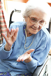 Elderly woman taking part in a Music and Movement therapy class,