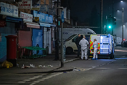 © Licensed to London News Pictures. 11/11/2020. Slough, UK. Forensic investigators gather evidence on Stoke Poges Lane. A person was reportedly stabbed in Slough on Tuesday 10/11/2020. A large cordon was put in place by Thames Valley Police centred around shops on Stoke Poges Lane and included a large section of Bradley Road. Photo credit: Peter Manning/LNP