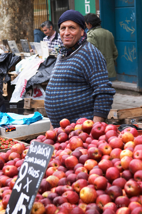 A street market merchant with a stall selling fruits and vegetables, a big pile of red delicious apples Montevideo, Uruguay, South America