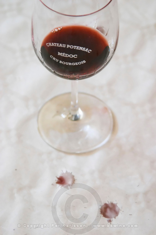 A glass of red wine inscribed with the name of the chateau with two drops of red wine on the white table top cloth Chateau Potensac Cru Bourgeois Ordonnac Medoc Bordeaux Gironde Aquitaine France