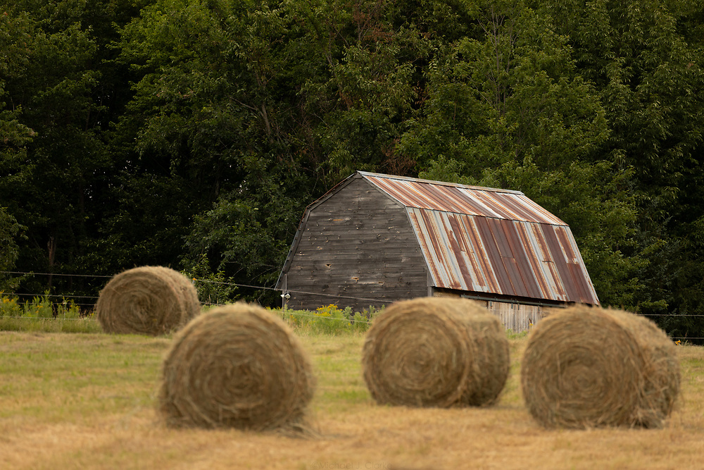 Hay bales lining a field in front an old barn in rural Vermont.
