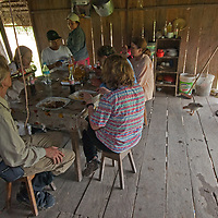 An adventure travel group enjoys lunch in a Yanayacu Indian hut in Peru's Amazon Jungle.