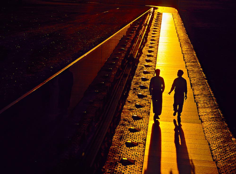 Two men walking next to the Vietnam Veterans Memorial at sunrise, Washington D.C., USA