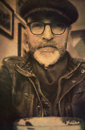 Male figure with grey beard wearing hat and glasses looking into the camera