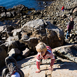 A boy (age 4) climbs a rock (as mom looks on) on the coast in Biddeford, Maine. Timber Point.