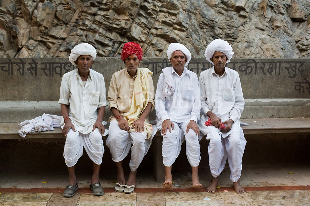 Four elderly Indian men sit and have their photograph taken after bathing in the pool at The Surya Mandir (known as the Monkey Temple), Jaipur, India