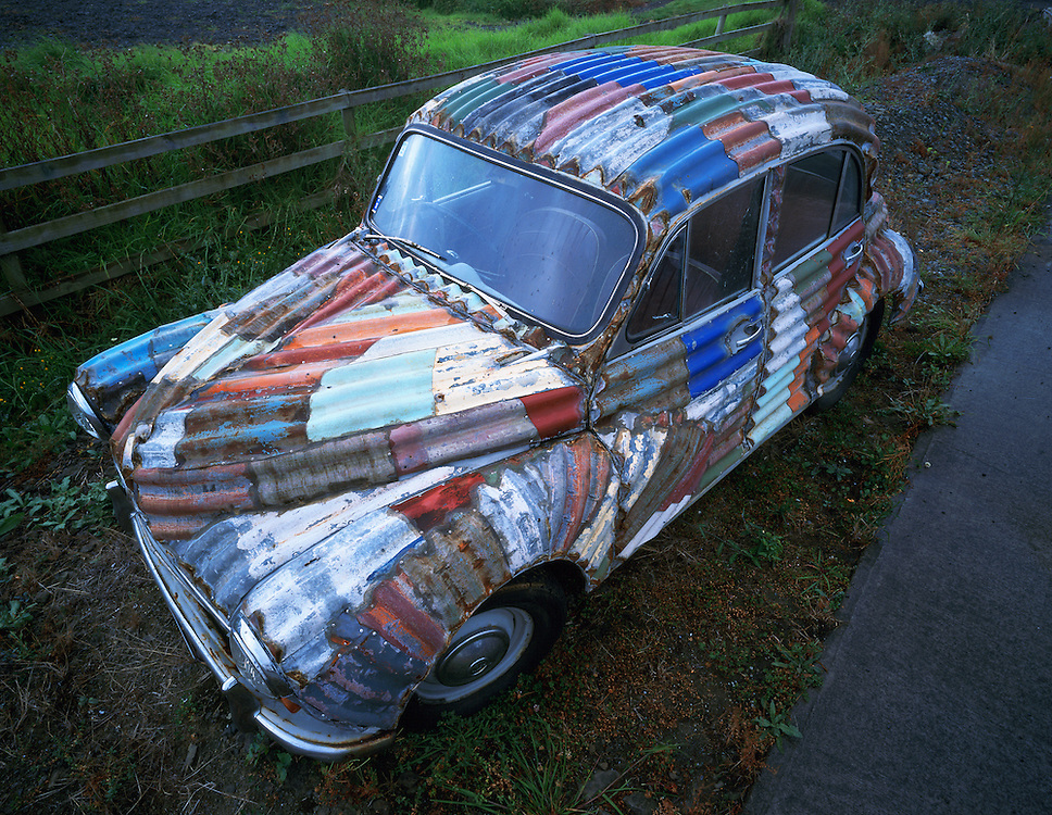 Artist Jeff Thomas sheaths his art sculptures in custom weathered corrugated tin roofing material for his signature look.  This Morris Minor is an example