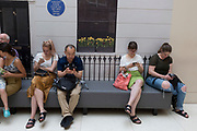 Art gallery visitors use their mobiles phones to access social media or check messages beneath a mocked-up exterior of the property where the artist Vincent van Gogh stayed in south London, on 4th August 2019, at Tate Britain, Millbank, London, England.