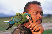 PARROT SOLDIER, Amazon, near Brazilian border, Venezuala, South America. Border guard soldier with parrot sitting on his shoulder. Ecological biosphere and fragile ecosystem where flora and fauna, and native lifestyles are threatened by progress and development. The rainforest is home to many plants and animals who are endangered or facing extinction. This region is home to indigenous primitive and tribal peoples including the Yanomami and Macuxi.