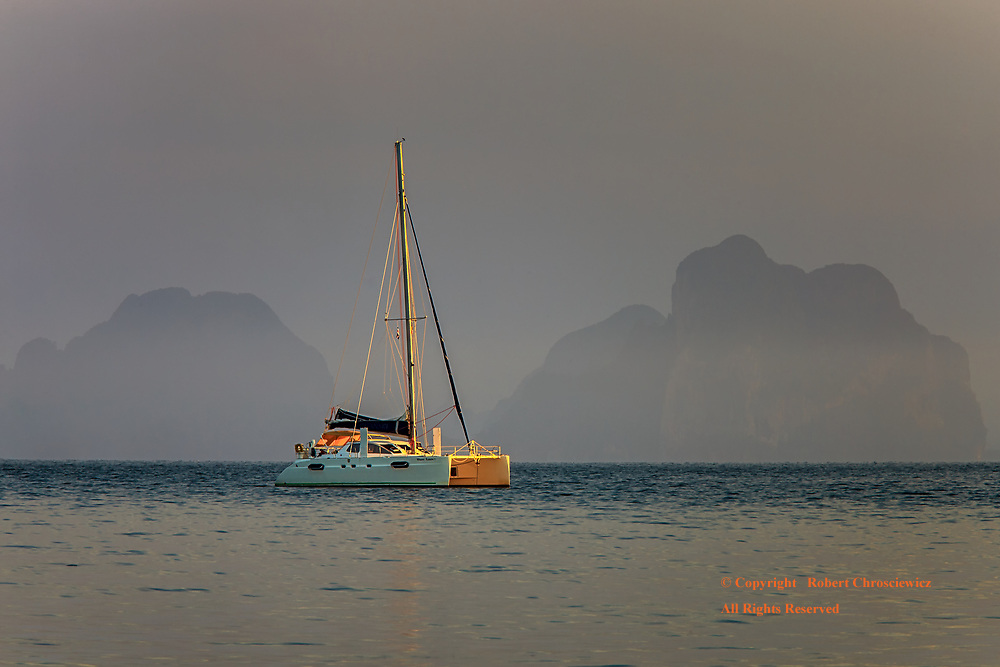 Misty Morning Yacht: An anchored sailing yacht is seen just off shore in the early morning mist, Ko Muk Thailand.