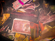 """10 AUGUST 2014 - BANGKOK, THAILAND: A stack of Hell Money in a burn barrel in Bangkok on the first day of Ghost Month. Hell money is a form of joss paper printed to resemble legal tender bank notes and is used in religious ceremonies in Chinese communities. The seventh month of the Chinese Lunar calendar is called """"Ghost Month"""" during which ghosts and spirits, including those of the deceased ancestors, come out from the lower realm. It is common for Chinese people to make merit during the month by burning """"hell money"""" and presenting food to the ghosts.    PHOTO BY JACK KURTZ"""
