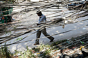 Passersby seen through a tangle of illegal electricity and water cables in the Munika area. New Delhi, India