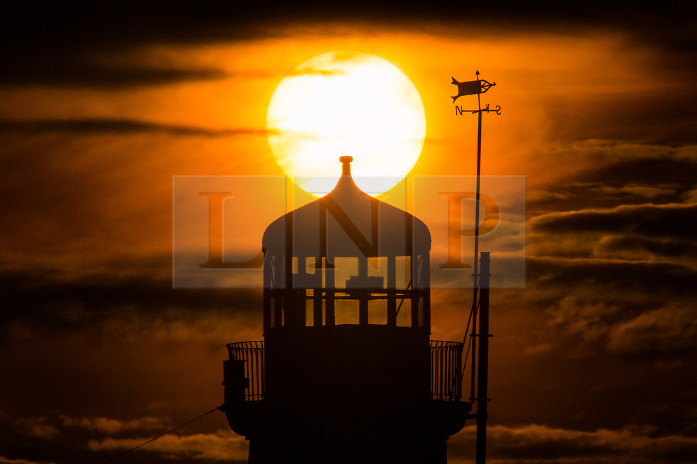 © Licensed to London News Pictures. 12/02/2019. Scarborough UK. The sun rises above Scarborough lighthouse this morning on the Yorkshire coast. Photo credit: Andrew McCaren/LNP