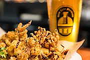 """Fried Calamari tossed with fried cherry peppers and drizzled with a balsamic glaze is accompanied by a pint of Abita Brewery's """"Purple Haze"""" at The Boathouse restaurant located at 31 Alvord Street in South Hadley on February 21, 2019. (Chris Marion / The Republican)"""