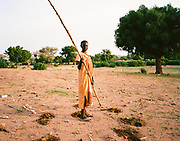 """NUBA MOUNTAINS, SUDAN – JUNE 9, 2018: A woman prepares to plant crops on the outskirts of Kouda, the cultural center of Hieban County.<br /> <br /> In 2011, the government of Sudan expelled all humanitarian groups from the country's Nuba Mountains. Since then, the Antonov aircraft has terrorized the Nuba people, dropping more than 4,080 bombs on hospitals, schools, marketplaces and churches. Today, vestiges of the Antonov riddle the landscapes of daily life, where more than 1 million Nuba live in famine conditions – quietly enduring the humanitarian blockade intended to drive them out of the region. The skies are mostly clear. Yet the collective memory of the bombings remains an open wound, and the Antonov itself a persistent threat. So frequent were the attacks that the Nuba nicknamed the high flying aircraft and its dismal hum: """"Gafal-nia ja,"""" they would declare, running to the hillsides. """"The loss of appetite has come."""""""