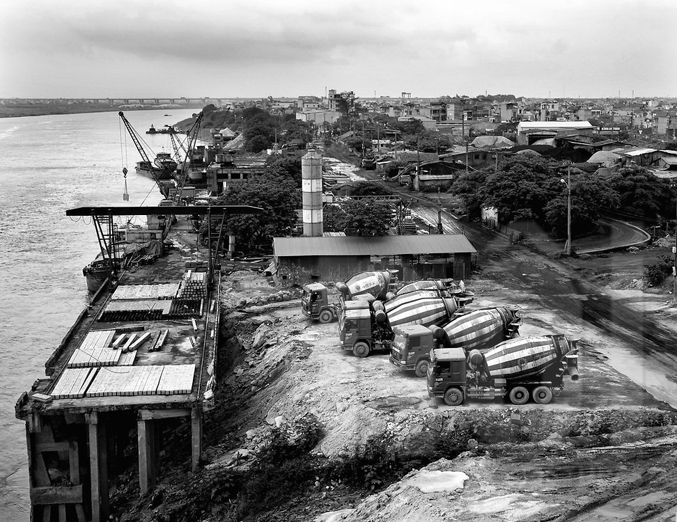 Cement mixer trucks are parked close a harbour along the red river. Hanoi, Vietnam, Asia. Cityscape of hanoi suburb in background.