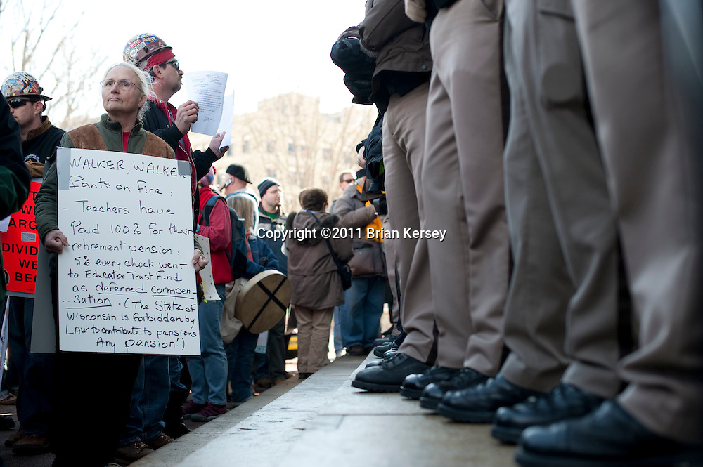 """Retired teacher Cecile Stelzer-Johnson (L) waits outside of the state Capital as police bar access to the building on March 1, 2011 in Madison, Wisconsin. Despite a court order issued Tuesday mandating that the state Capitol should be opened to the public """"during business hours and at times when governmental matters, such as hearings, listening sessions and court arguments are being conducted"""" the Capitol remained closed to the public.  (Photo by Brian Kersey)"""