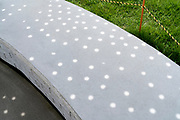 detail of clean grey ornamental concrete bench sprinkled with dots of light