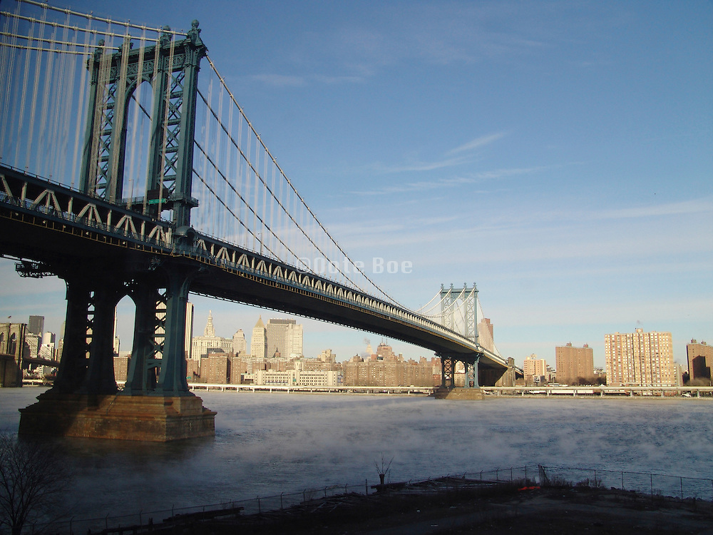 Early morning view of Manhattan Bridge with mist on the East River.